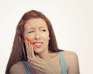 'woman in pain after wisdom tooth extraction'