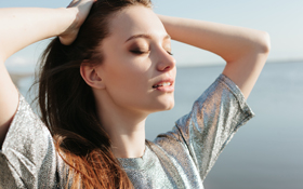 Girl inhales the fresh sea air after her sinus lift surgery in San Francisco.
